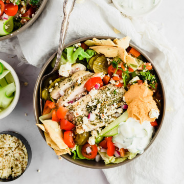 loaded salad bowl with sliced grilled chicken, pita chips, tomatoes, red onions, pickles, dollop of hummus, tabbouleh, and tzatziki dressing with surrounding ingredients around it