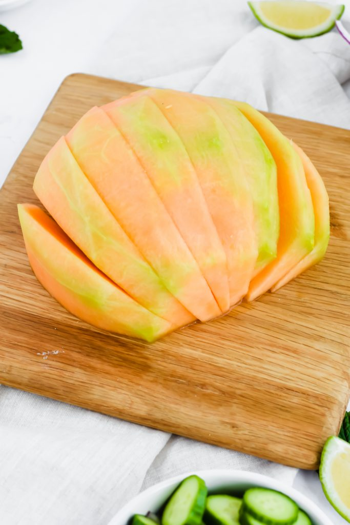 half of a cantaloupe partially sliced on wood cutting board and other ingredients around it