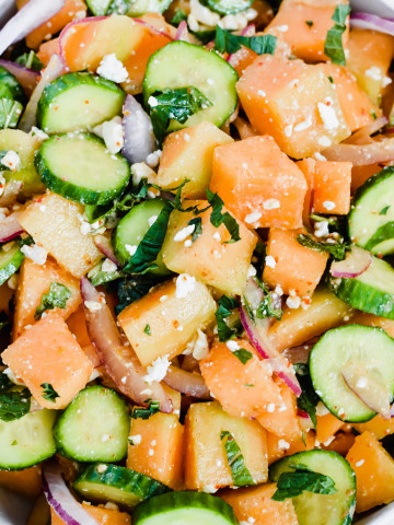 close up image of cantaloupe cucumber feta mint salad all tossed together and fresh pepper on top
