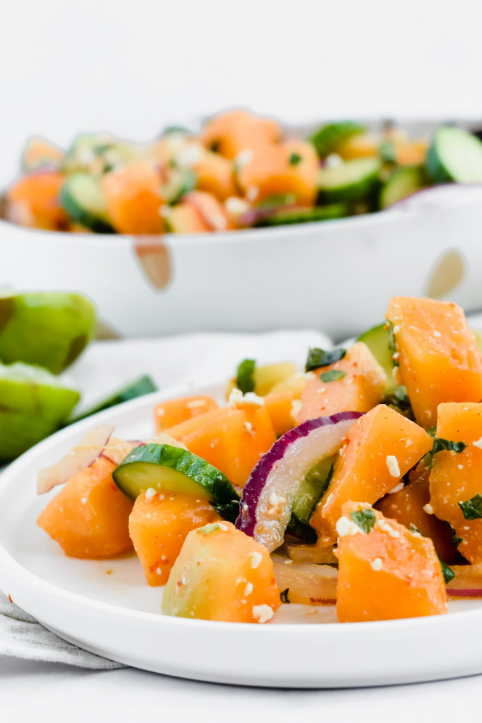 90 degree angled image of cantaloupe salad served on white dish with main serving bowl in the background