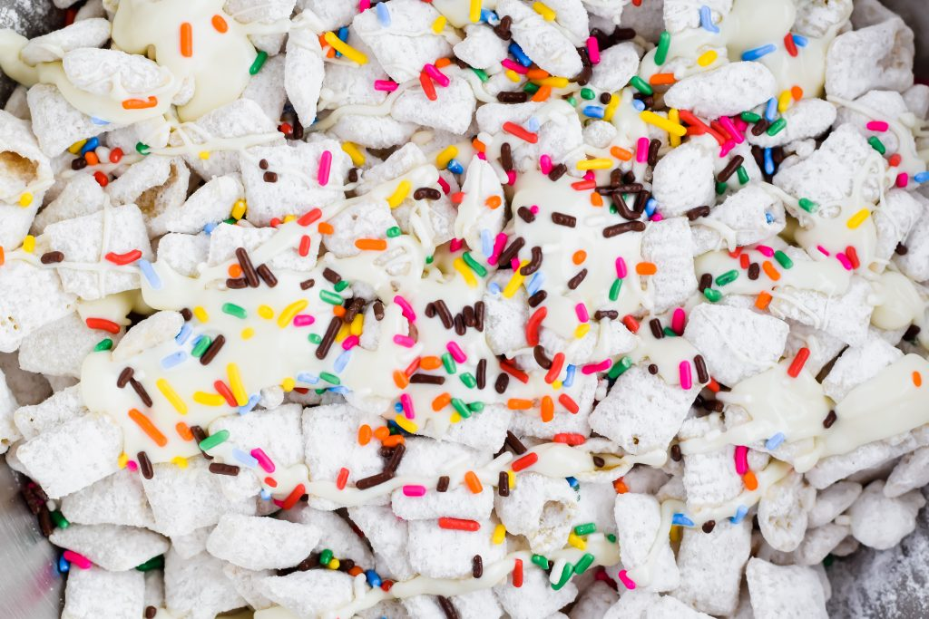 close up view of coated birthday cake puppy chow with melted white chocolate and spinkles