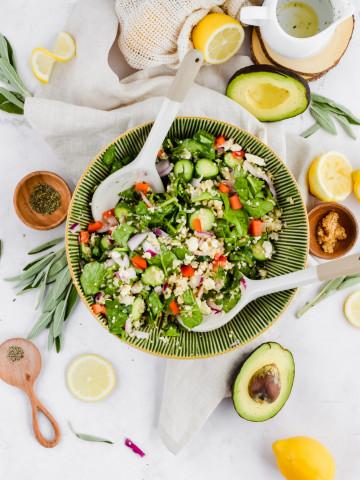 tossed salad in green salad bowl garnished with lemon slices, avocado, and olive oil