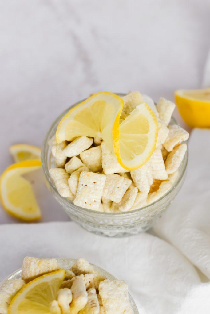 glass parfait dish holding lemon puppy chow recipe with fresh lemon swirl on top