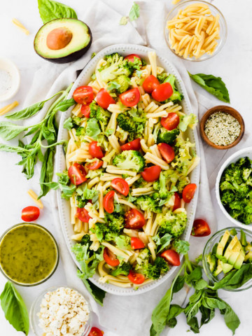 large pasta salad plate filled with vegetables and surrounded by garnishings