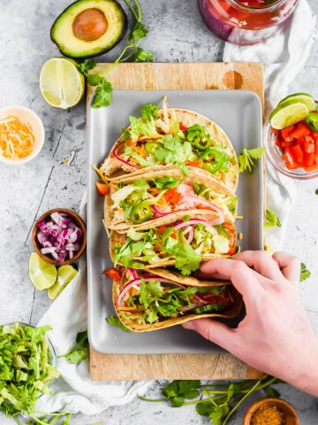 hand holding one taco out of four on the platter with a ton of garnish