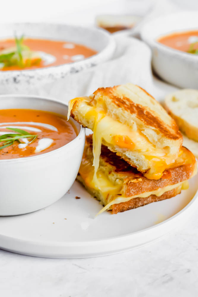 bowl of tomato soup with two pieces of grilled cheese aside it with cheese pull