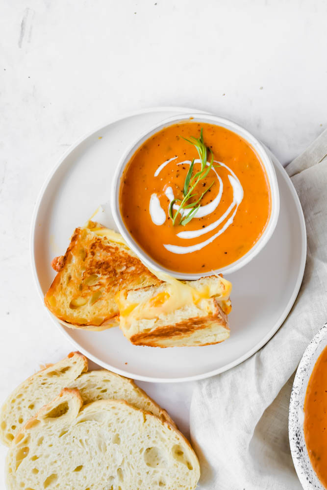 bowl of tomato soup with two pieces of golden brown bread and cheese on white plate