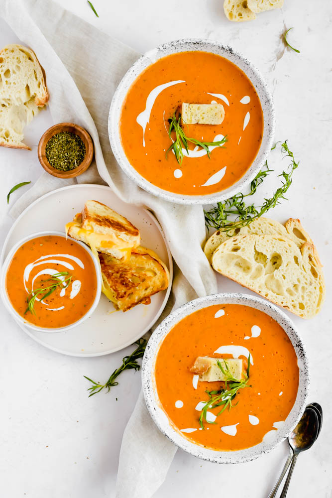 three bowls of tomato soup with grilled cheeses and slices of bread on white background