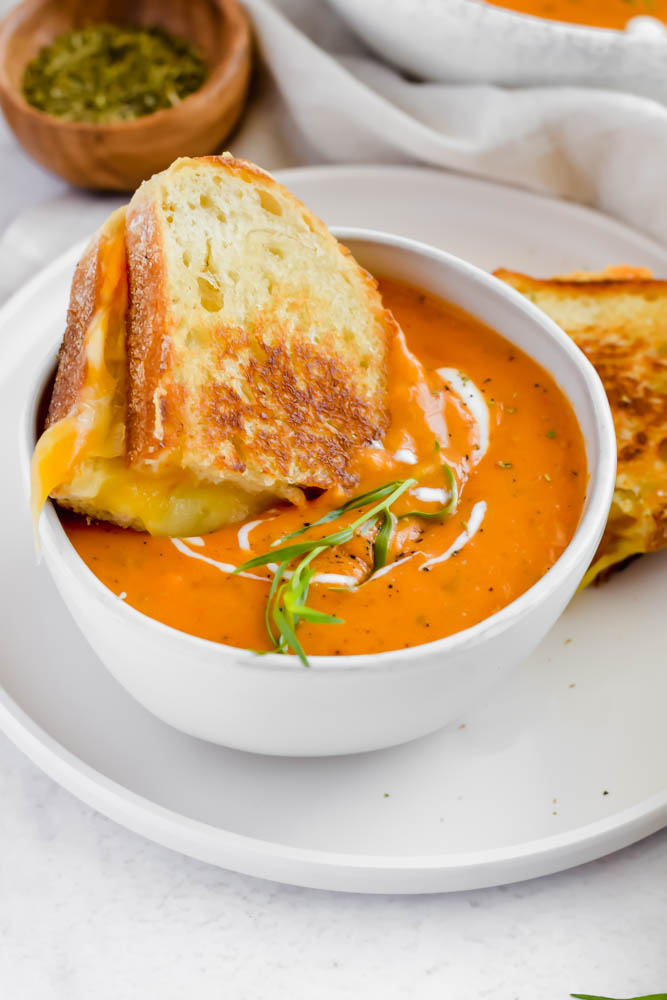 piece of grilled cheese being dunked into a big bowl of roasted tomato soup
