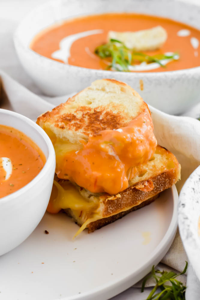 stacked grilled cheese sandwich dunked in roasted tomato soup on white plate