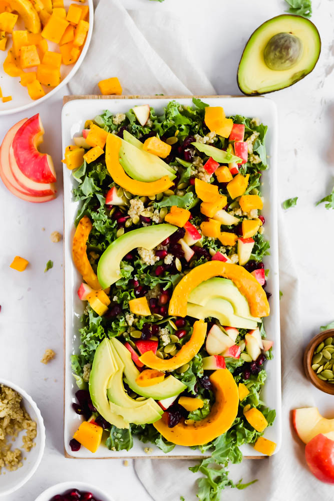 rectangular platter filled with kale butternut squash and fruit salad garnished with avocado and dried cranberries