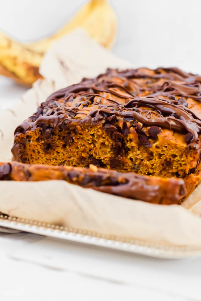 close up image of pumpkin banana bread loaf with one slice cut off