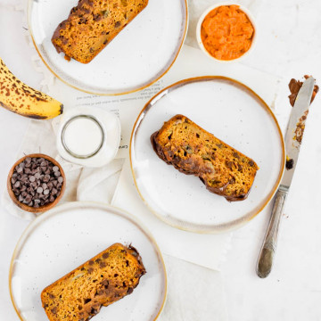 three plates with slices of pumpkin banana bread garnished with chocolate drizzle and ingredients around it
