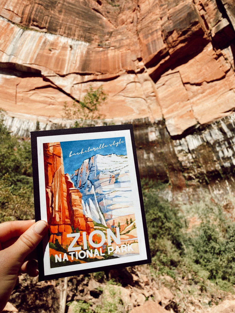 hand holding Zion National Park poster in front of mountains