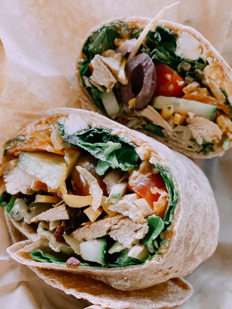 greek wrap loaded with veggies and half ate