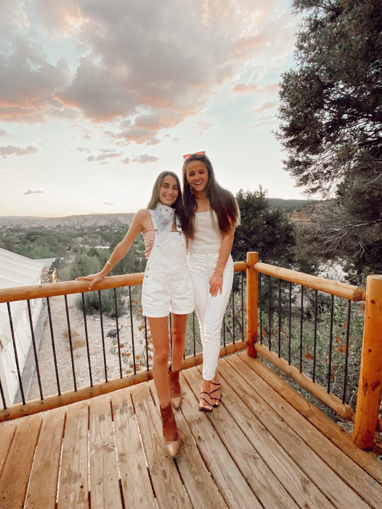 two girls standing on a deck overlooking the sunset