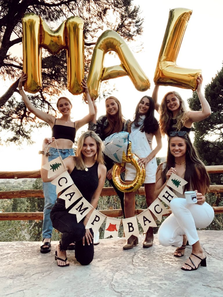 six girls holding balloons and sign to celebrate the bride