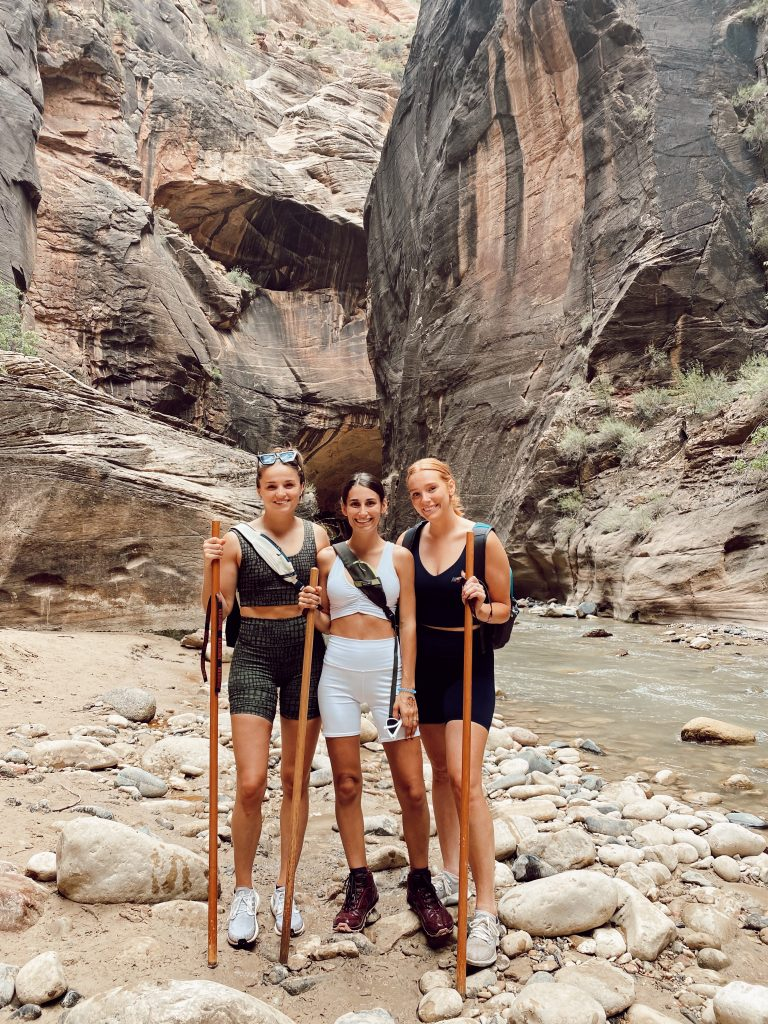 three girls with hiking sticks in the middle of the Narrows in Zion National Park