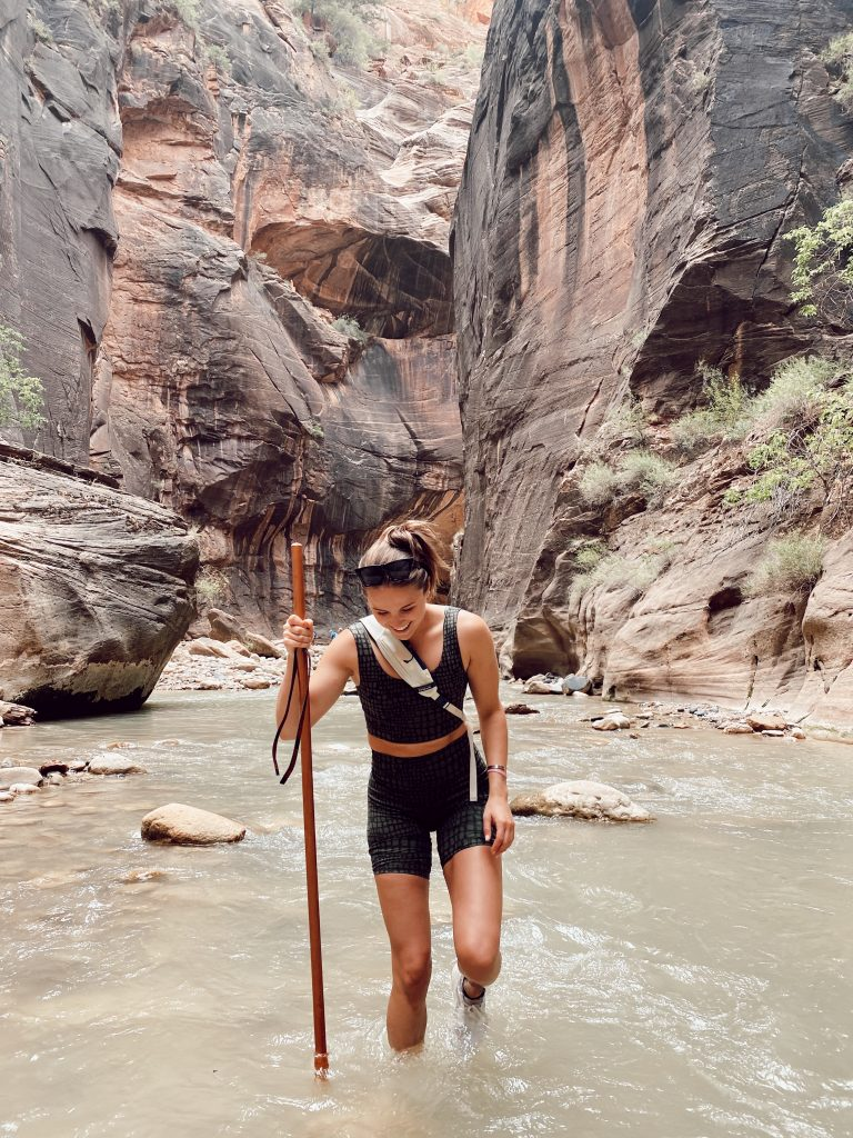 Girl smiling in water hiking with large stick in the middle of the Narrows