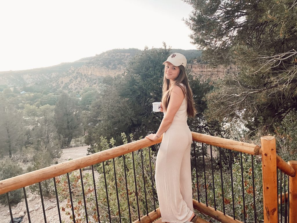 girl standing with mug on a balcony overlooking the mountains