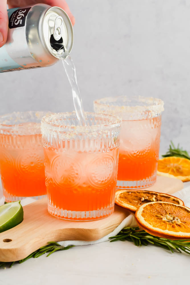 hand pouring club soda beverage to top off Italian Margarita cocktail