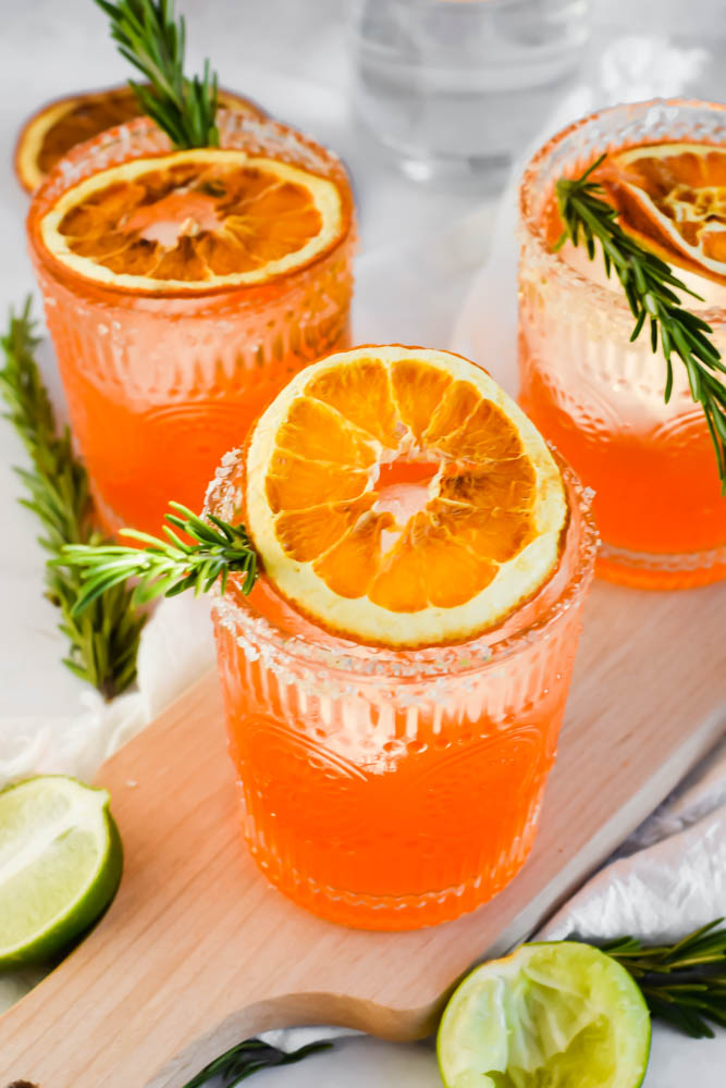 three Italian Margaritas garnished with fresh rosemary and dried oranges