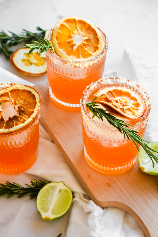 three Italian Margaritas garnished with fresh rosemary and dried oranges and limes on the side