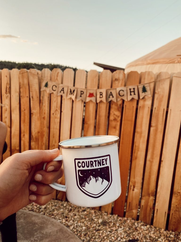 campfire mug that says courtney with wooden fence behind it