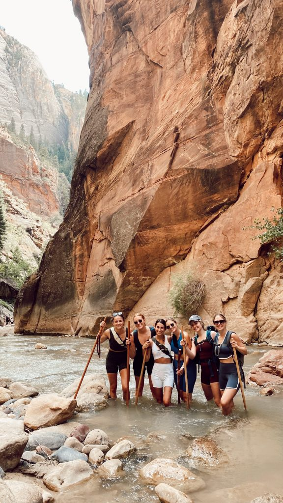 six girls in athletic gear standing on a rock in the middle of the Narrows in Zion National Park
