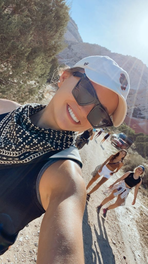 smiling girl in hat and sunglasses with sun peaking through