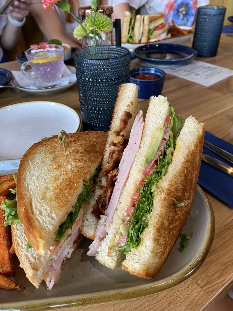 double stacked turkey bacon avocado club sandwich on a plate