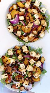 two bowls of salad topped with caramelized onions, peaches, balsamic dressing and feta cheese