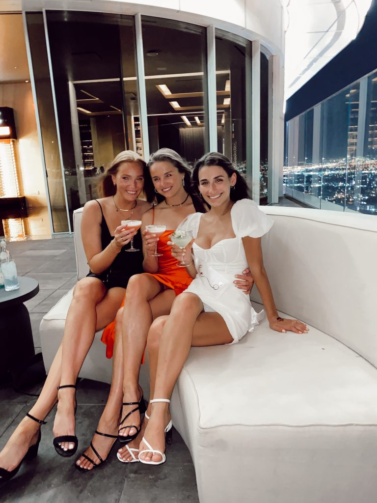 three girls holding drinks sitting on white booth with skyline in the background