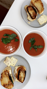 two bowls of tomato soup topped with basil and grilled sandwiches on the side