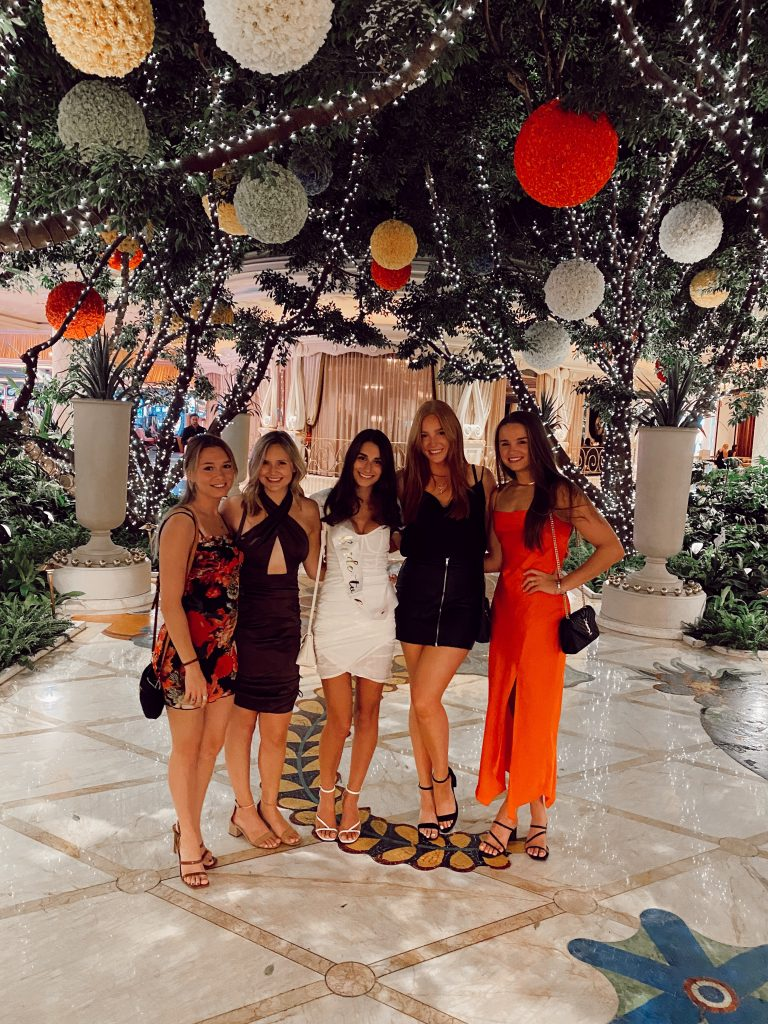 five girls dressed in club attire with lanterns hanging above them