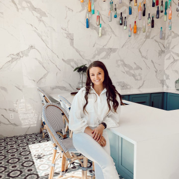 girl smiling and sitting down in a large white kitchen